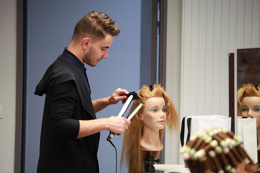 Un apprenti coiffe une tête