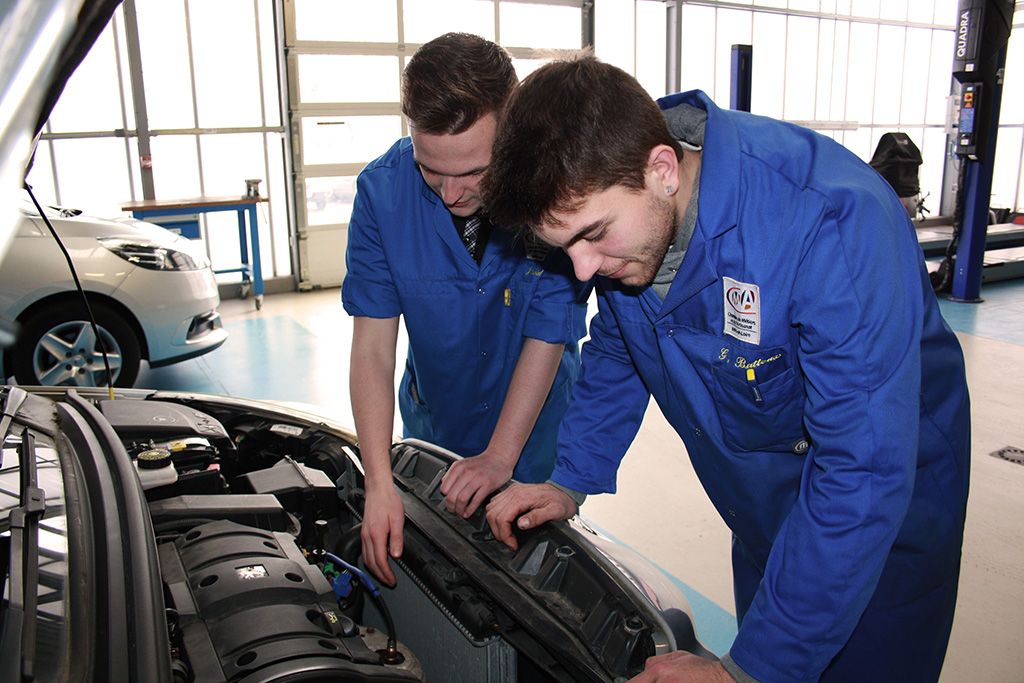 deux apprentis regarde un moteur de voiture